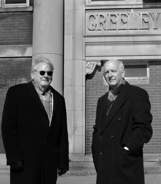 Photo by Clare Howard Sandy Farkash, left, and John Meisinger, former principals in Peoria public schools, stand in front of the shuttered Greeley School on NE Jefferson Avenue. The two retired principals are meeting with business, political and community leaders to coordinate efforts to remove incumbents from the School Board. They are urging people to vote on April 7, but they are not endorsing a candidate.