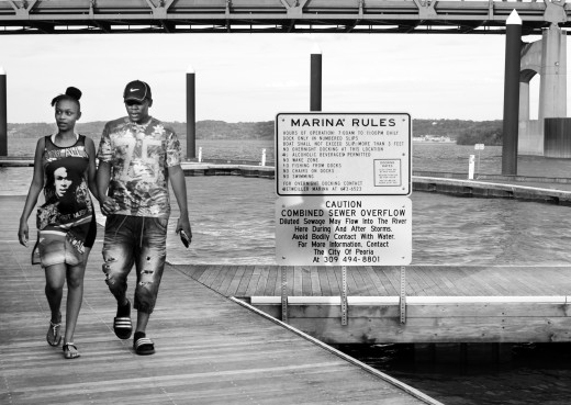 Peorians Shanterryona Anderson and Marcus Shockley walk on a Sunday evening along the Illinois River on the boat docks near the Murray Baker Bridge. Signs along the docks warn that during and following heavy rains, sewage is dumped into the river. Despite the signage, most people don't realize raw sewage enters the river at that point near the downtown public marina and the Spirit of Peoria paddlewheel.