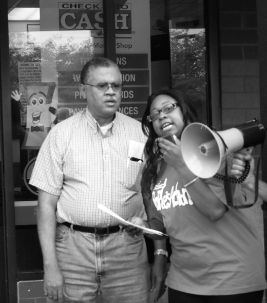 The Rev. Tony Pierce, Heaven's View Church, protests outside a payday loan store in Campustown with Candice Byrd, of Bloomington, who is trapped by a payday loan she took out without understanding the high interest rates she was paying. The protest was organized by Illinois People's Action, a faith-based community organization focused on social justice.