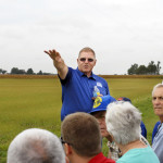 PHOTO BY CLARE HOWARD  Organic farmer Harold Wilken points to his corn acreage during a tour of his Danforth fields with other farmers and organic advocates who gathered from throughout the Midwest to discuss contamination of organic crops from fields planted with GM seeds. The problem is costing organic farmers tens of thousands of dollars annually, and the corporate patent holders of GM seeds are not compensating them for their loss. The USDA is researching the problem and possible solutions.