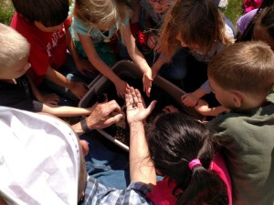 """PHOTO BY ROGER LARSON A close-up examination of a worm is the highlight of """"Worm Day"""" for 10 children at the Peoria Heights Public Library garden project."""