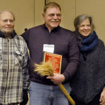 PHOTO BY CLARE HOWARD Harold Wilken holds his plaque and a sheaf of organic red winter wheat flanked by Herman Brockman, left, and Terra Brockman following the award ceremony recognizing Wilken as the 2016 R.J. Vollmer Award winner for sustainable agriculture. Herman Brockman reached out to Wilken nearly two decades ago about leasing Brockman family land to farm organically. Terra Brockman is the governor's appointee on the Illinois Sustainable Agriculture Committee.