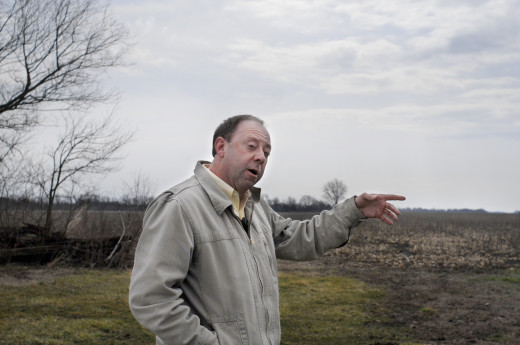 PHOTO BY CLARE HOWARD Farm manager Rob Woodrow points to land that will be planted in organic pumpkin this spring in the second year of a 36-month transition from chemical farming to organic production. He uses tillage radish, sunn hemp and cereal rye as cover crops. Woodrow has studied organic practices for years and is implementing some recent research from Rodale Institute and Western Illinois University. He expects a new transitional organic label will facilitate a shift of thousands of acres of farmland from chemical to organic practices.