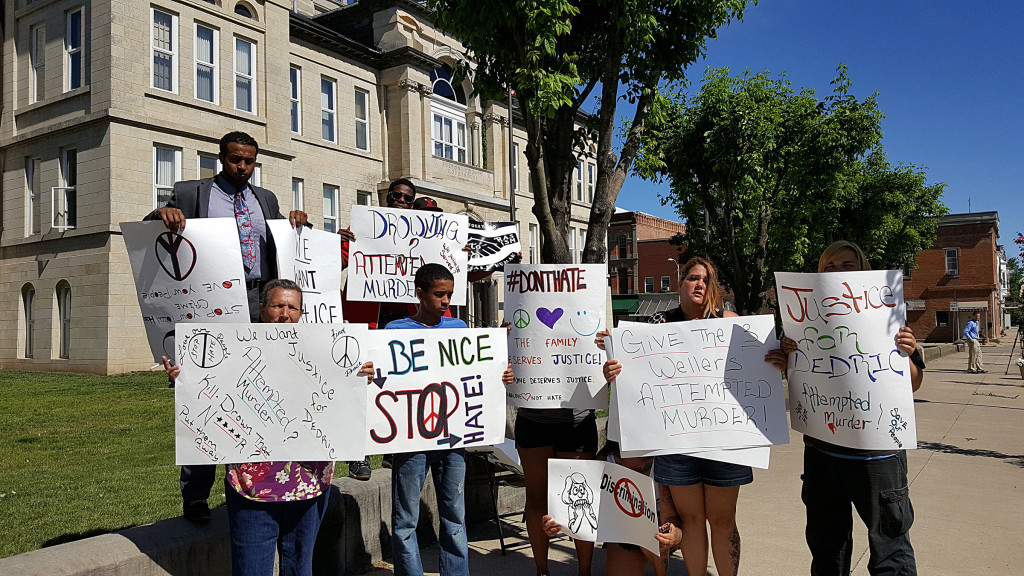 PHOTO BY BILL KNIGHT A small group demonstrates outside the Fulton County Courthouse June 29 while people accused of a hate crime appear at a preliminary hearing.