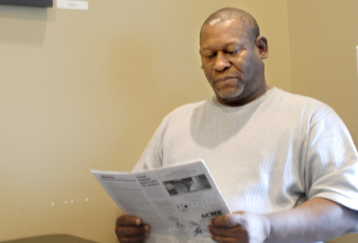 PHOTO BY CLARE HOWARD  Steve Heidelberg reads articles from past issues of Community Word about the 1970 trial of his father Cleve Heidelberg for the killing of a Peoria County Sheriff's deputy. A recent investigation into the crime and trial are revealing inconsistencies and problems that have convinced some people of Cleve Heidelberg's innocence.