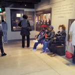 PHOTO BY SHERRY CANNON Visitors to the new Smithsonian National Museum of African American History and Culture work their way through exhibits that depict the often untold story of our nation from 1501, the start of a brutal, dehumanizing slave trade. Ultimately, 12 million enslaved African people were shipped in horrendous conditions to the Americas, and the trade continued even as the colonies fought for freedom from Great Britain. Bobbi Mallory, niece of author Sherry Cannon, is sitting on bench at right.