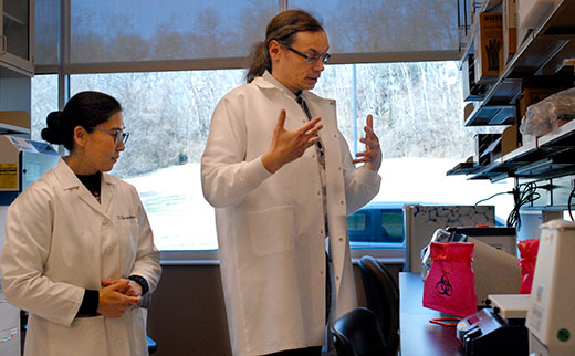 Yajing Song and Peter Gyarmati examine equipment set up in their new research lab at University of Illinois College of Medicine at Peoria. They study the gut microbiome and its links to cancer and other diseases.