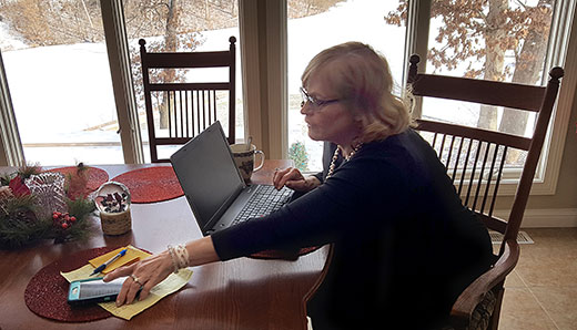 Karen Hudson works at her desk in her rural Peoria County home. After two years of legal haggling, a contempt of court charge against Hudson was summarily reversed by the Fourth District Appellate Court. The charges against Hudson stemmed from allegations by representatives of a CAFO that was in court over nuisance complaints. The contempt of court charge against Hudson was then used as justification to declare a mistrial.