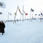 Eliida Lakota stands before flags of more than 90 Native Nations flying in defiance of the Dakota Access Pipeline route across Indian lands and under the Missouri River. Lakota traveled to Standing Rock Sioux Reservation in North Dakota to pray with the protesters, to learn and to assist with operation of the encampment. Despite a wind chill of 45 below zero, about 500 campers remain, including veterans from around the country.